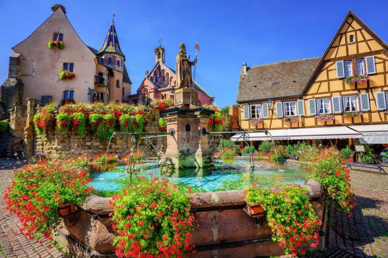 """در اعماق کلمار (Colmar) منطقه آلزاس (Alsace) شمال شرقی فرانسه (بهترین مکان برای صرف نوشیدنی های خوشمزه)، با شهر منحصر به فردی آشنا می شوید که """"اگوییسهایم"""" (Eguisheim) نام دارد. اگوییسهایم 1413 کیلومترمربع مساحت و 1572 نفر جمعیت دارد و 210 متر بالاتر از سطح دریا واقع شده است. اگوییسهایم از لحاظ تاریخی شهری جداگانه و دارای هویتی منحصر به فرد است."""
