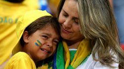 A young Brazil fan is consoled after being defeated