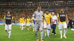 Julio Cesar (C) and players of Brazil walk off the pitch