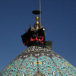 برافراشته شدن پرچم حضرت اباعبدالله الحسین ع بر فراز گنبد فیروزه ای شهر شیراز