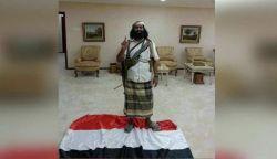 """فرمانده القاعده  در کاخ ریاست جمهوری در شهر """"المکلا"""" در جنوب یمن، روی پرچم این کشور ایستاده است."""